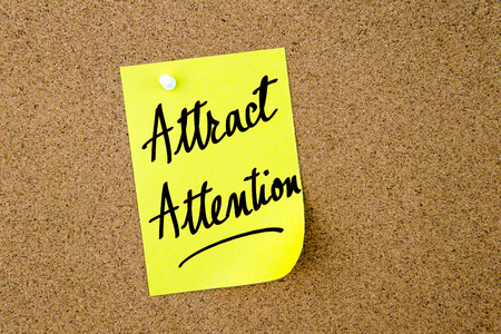 attract: Attract Attention written on yellow paper note pinned on cork board with white thumbtacks, copy space available Stock Photo