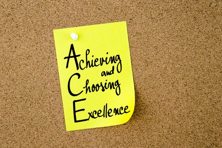 achieving: ACE Achieving and Choosing Excellence written on yellow paper note pinned on cork board with white thumbtacks, copy space available