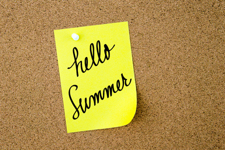 cork sheet: Hello Summer written on yellow paper note pinned on cork board with white thumbtacks, copy space available Stock Photo