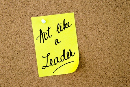 cork sheet: Act Like A Leader written on yellow paper note pinned on cork board with white thumbtacks, copy space available Stock Photo