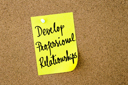 yellow thumbtacks: Develop Professional Relationships written on yellow paper note pinned on cork board with white thumbtacks, copy space available Stock Photo