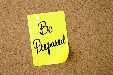 be prepared: Be Prepared written on yellow paper note pinned on cork board with white thumbtacks, copy space available