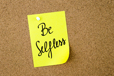 selfless: Be Selfless written on yellow paper note pinned on cork board with white thumbtacks, copy space available