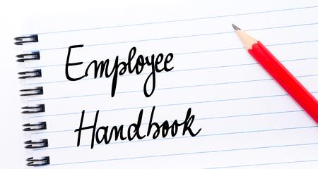Employee Handbook geschreven op notebook pagina met rood potlood op de rechter