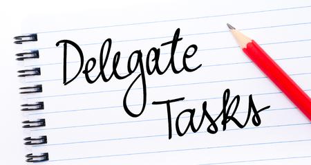 delegar: Delegar tareas escritas en la p�gina del cuaderno con el l�piz rojo a la derecha Foto de archivo