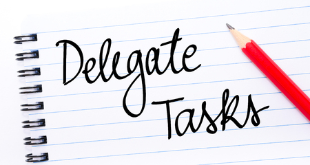 delegar: Delegate Tasks written on notebook page with red pencil on the right