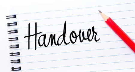 handover: Handover written on notebook page with red pencil on the right Stock Photo