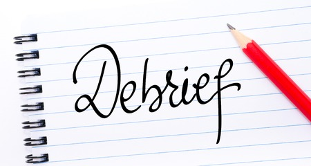 Debrief written on notebook page with red pencil on the right