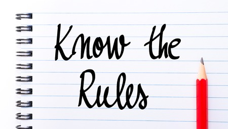 comunicaci�n escrita: Know The Rules written on notebook page with red pencil on the right Foto de archivo
