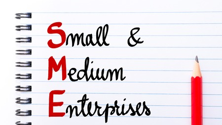 enterprises: SME Small and Medium Enterprises written on notebook page with red pencil on the right