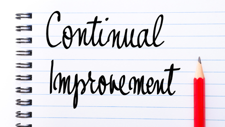 comunicación escrita: Continual Improvement written on notebook page with red pencil on the right