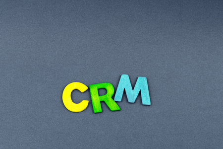 definition define: Business Abbreviation CRM as Customer Relationship Management created of wood letters on dark background, copy space available