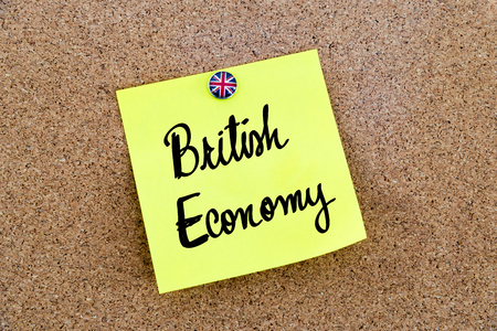 great britain flag: Yellow paper note pinned on cork board with Great Britain flag thumbtack, written text BRITISH ECONOMY , United Kingdom exit from European Union