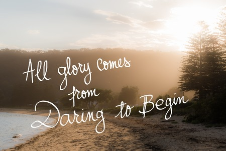 daring: All Glory Comes From Daring To Begin message. Handwritten motivational text over sunset calm sunny beach background with vintage filter applied Stock Photo