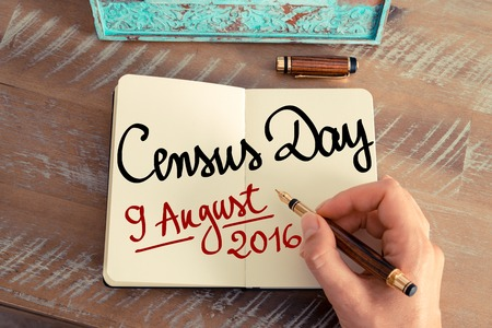 census: Retro effect and toned image of a woman hand writing a note with a fountain pen on a notebook. Handwritten text Census Day 9 August 2016, Australia as concept image Stock Photo