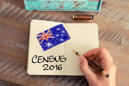 census: Retro effect and toned image of a woman hand drawing the Australian Flag with a fountain pen on a notebook. Concept image with CENSUS 2016 and Australian flag