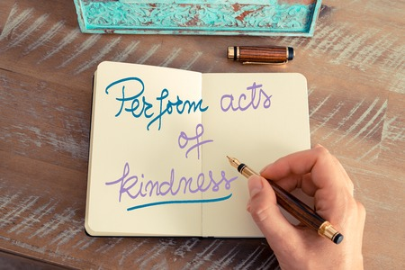 Retro effect and toned image of a woman hand writing a note with a fountain pen on a notebook. Handwritten text Perform Acts of Kindness as success and evolution concept image Stock Photo