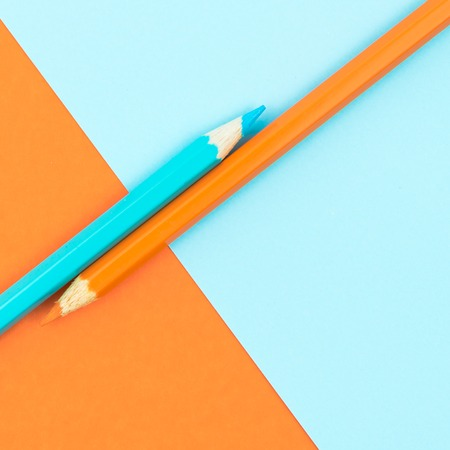 Orange and Turquoise coloured pencils and paper, abstract contrast conceptual image