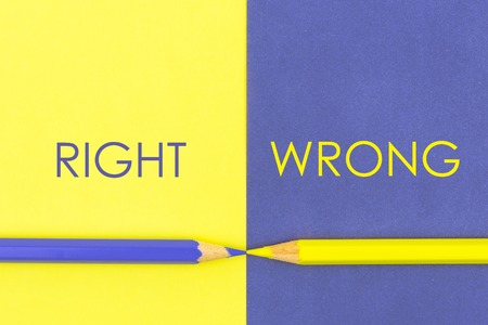 Right versus Wrong contrast concept . Yellow and Violet coloured pencils and paper.