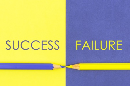 Success versus Failure contrast concept . Yellow and Violet coloured pencils and paper.
