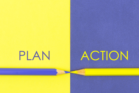versus: Plan versus Action contrast concept . Yellow and Violet coloured pencils and paper. Stock Photo