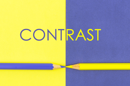 Word CONTRAST. Yellow and Violet coloured pencils and paper, abstract contrast conceptual image