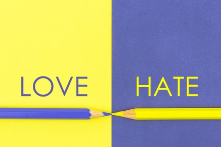 versus: Love versus Hate contrast concept . Yellow and Violet coloured pencils and paper.