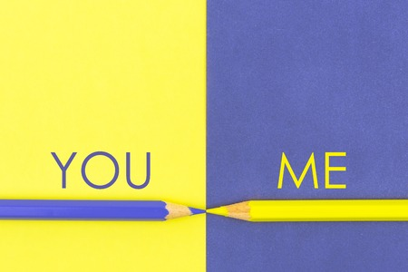 versus: You versus Me contrast concept . Yellow and Violet coloured pencils and paper.