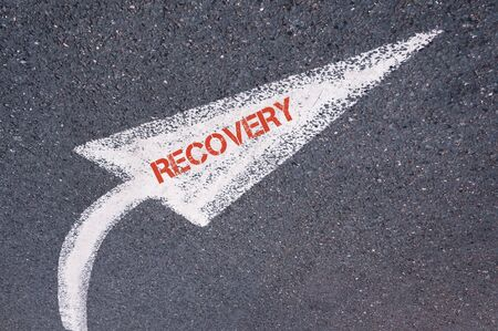 road to recovery: Directional white painted arrow with word RECOVERY over road surface, concept image