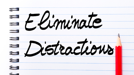comunicaci�n escrita: Eliminate Distractions written on notebook page with red pencil on the right as Business Concept Foto de archivo