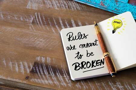 broken strategy: Retro effect and toned image of notebook next to a fountain pen. Business concept image with handwritten text RULES ARE MEANT TO BE BROKEN, copy space available, light bulb as smart idea Stock Photo