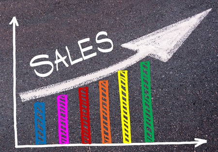 directional arrow: Colorful graph drawn over tarmac and word SALES with directional arrow, business design concept Stock Photo