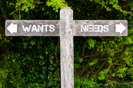 wants: Wooden signpost with two opposite arrows over green leaves background. WANTS versus NEEDS directional signs, Choice concept image
