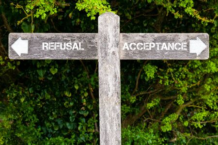 refusal: Wooden signpost with two opposite arrows over green leaves background. REFUSAL versus ACCEPTANCE directional signs, Choice concept image Stock Photo