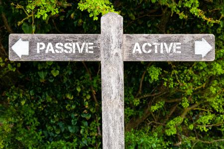 Houten wegwijzer met twee tegengestelde pijlen over groene bladeren achtergrond. image Passief versus Actief richtingborden, concept van de keus