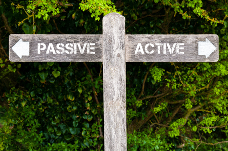 Wooden signpost with two opposite arrows over green leaves background. Passive versus Active directional signs, Choice concept image