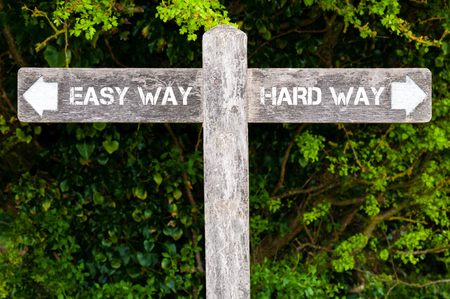 easy way: Wooden signpost with two opposite arrows over green leaves background. Easy Way versus Hard Way directional signs, Choice concept image