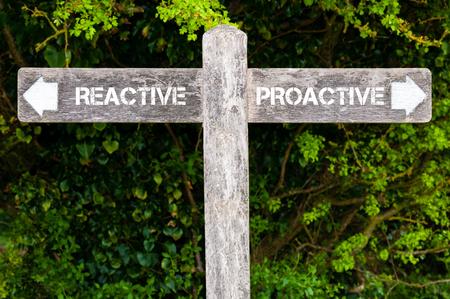 Houten wegwijzer met twee tegengestelde pijlen over groene bladeren achtergrond. image reactieve versus Proactive richtingborden, concept van de keus