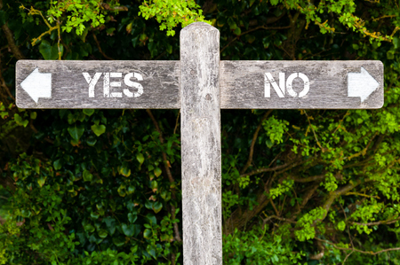 Wooden signpost with two opposite arrows over green leaves background. YES versus NO directional signs, Choice concept image Stock Photo