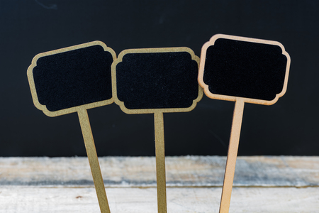 Wooden mini blackboard labels over chalkboard background and table, copy space available