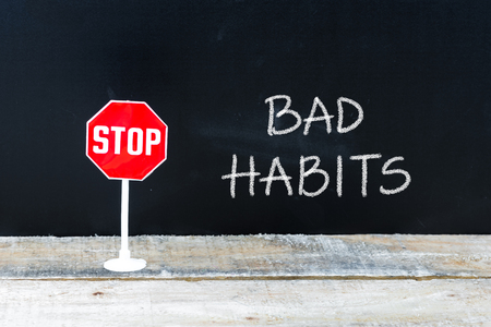 bad habits: Mini STOP sign over chalkboard background and table, STOP BAD HABITS concept Stock Photo