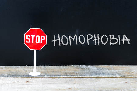 homophobia: Mini STOP sign over chalkboard background and table, STOP HOMOPHOBIA concept Stock Photo