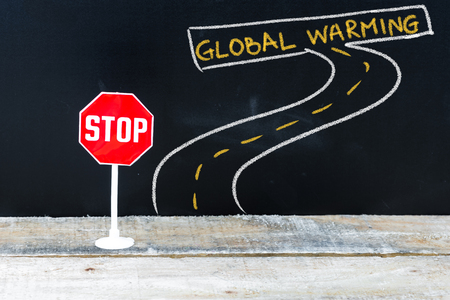 stop global warming: Mini STOP sign on the road to GLOBAL WARMING, hand drawing over chalkboard