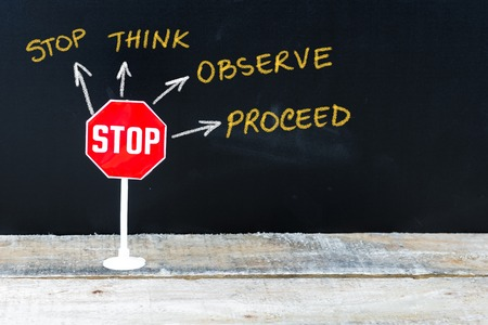 proceed: Mini STOP sign as Stop, Think, Observe and Proceed, hand drawing over chalkboard