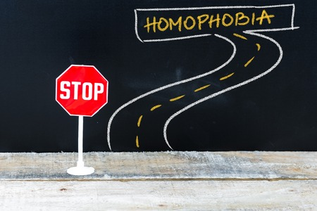 homophobia: Mini STOP sign on the road to HOMOPHOBIA, hand drawing over chalkboard