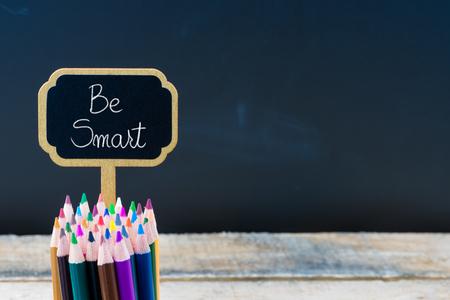木製ミニ黒板メッセージがスマートにラベルを付けて、スペース、利用可能な教育コンセプトをコピー黒板背景に鉛筆を着色