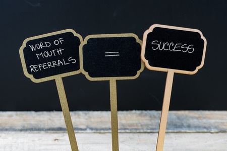 referrals: Business message WORD OF MOUTH REFERRALS EQUALS SUCCESS written with chalk on wooden mini blackboard labels, defocused chalkboard and wood table in background