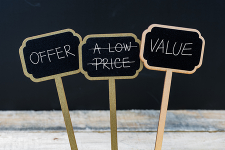 low price: Business message OFFER VALUE INSTEAD OF LOW PRICE written with chalk on wooden mini blackboard labels, defocused chalkboard and wood table in background Stock Photo