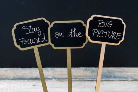 big picture: Business message STAY FOCUSED ON THE BIG PICTURE written with chalk on wooden mini blackboard labels, defocused chalkboard and wood table in background