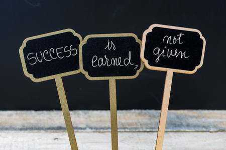 earned: Business message SUCCESS IS EARNED, NOT GIVEN written with chalk on wooden mini blackboard labels, defocused chalkboard and wood table in background